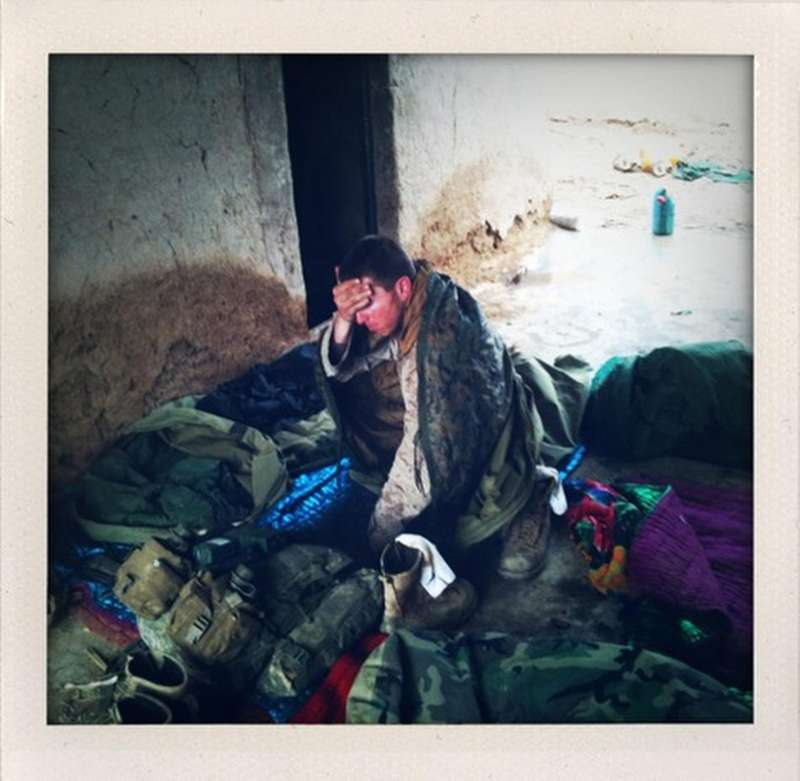 A U.S. Marine wakes up in the morning after sleeping with his platoon in a mud walled compound in Marjah in Afghanistan's Helmand province.