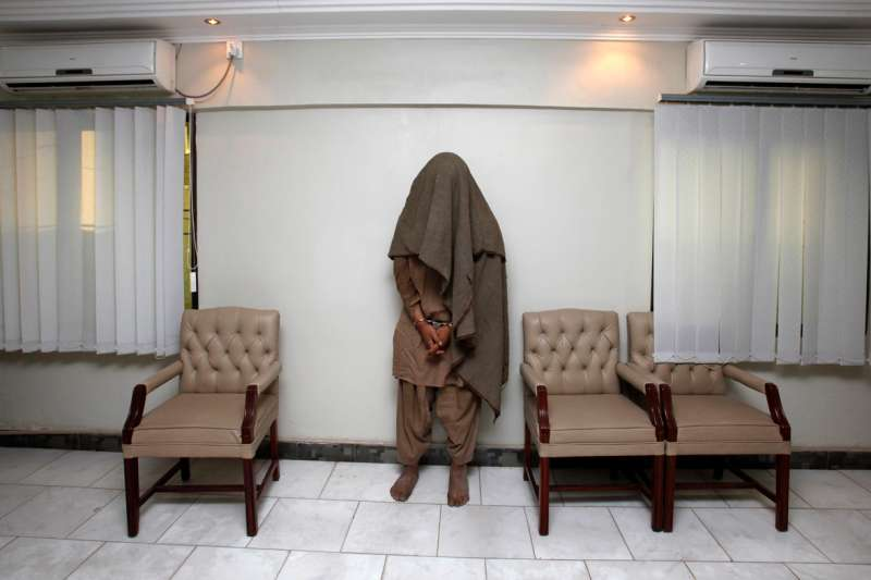 Karachi, Pakistan: An arrested member of the outlawed militant group Lashkar-e-Jhangvi is presented to the media at the Police Crime Investigation Department in Karachi, March 29, 2010. Police had earlier arrested three members of the outlawed Sunni militant group and seized up to 60 kg (132 lbs) of explosives and detonators.