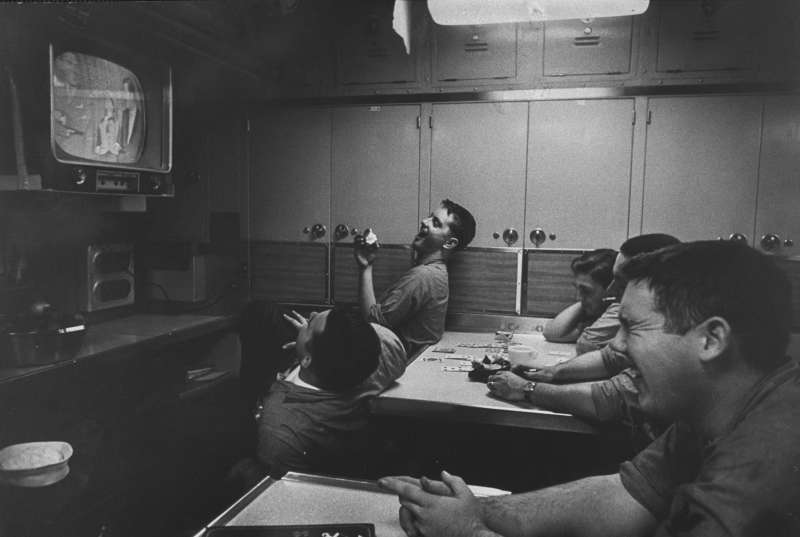 Men watch  at a submarine base and school.