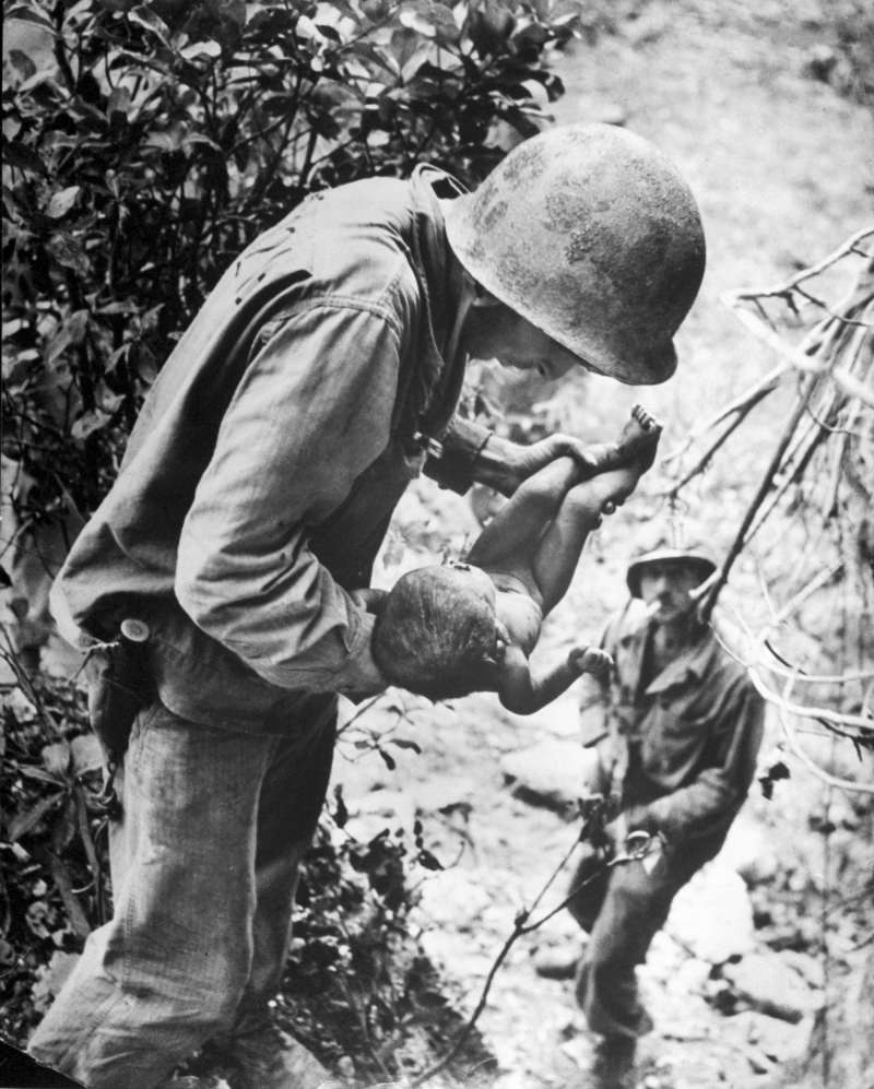 In a W. Eugene Smith photo that, somehow, captures both tenderness and horror, a U.S. Marine cradles a near-dead infant that the Marine found wedged, face down, literally under a rock while clearing out Japanese soldiers hiding in caves on Saipan, in the Mariana Islands. Hundreds of Japanese civilians in the islands committed suicide rather than surrender to the Americans.