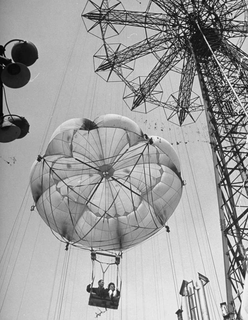 Thrillseekers ride the 300-foot parachute jump at Coney Island.