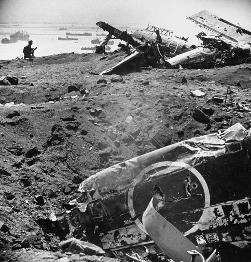 Warplanes Litter the Beach at Iwo Jima                              As American ships invade Iwo Jima in Februay 1945, Japanese airplanes lie wrecked on the beach, but ground troops will defend the island fiercely for 35 days.