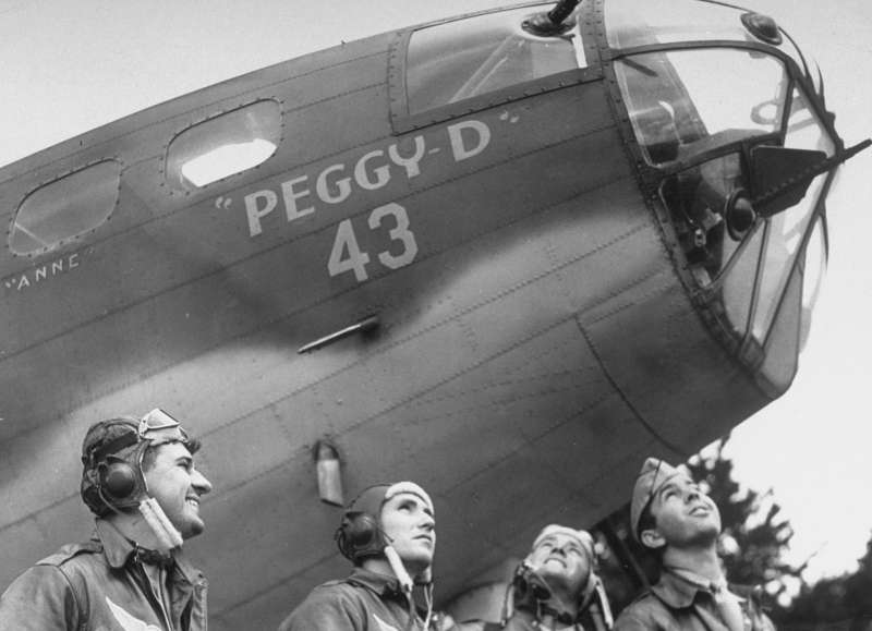 Four U.S. airmen pose by their B-17 in southern England, 1942.