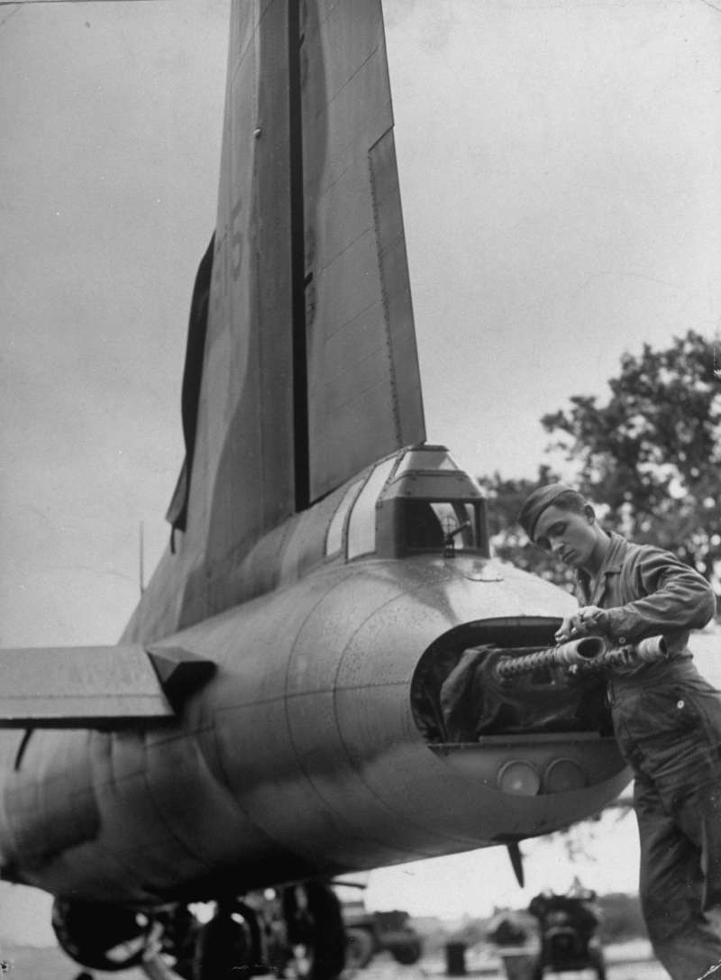 A B-17 Flying Fortress tail gunner cleans machine guns he recently used to down a German plane in a bombing raid over Europe in 1942.