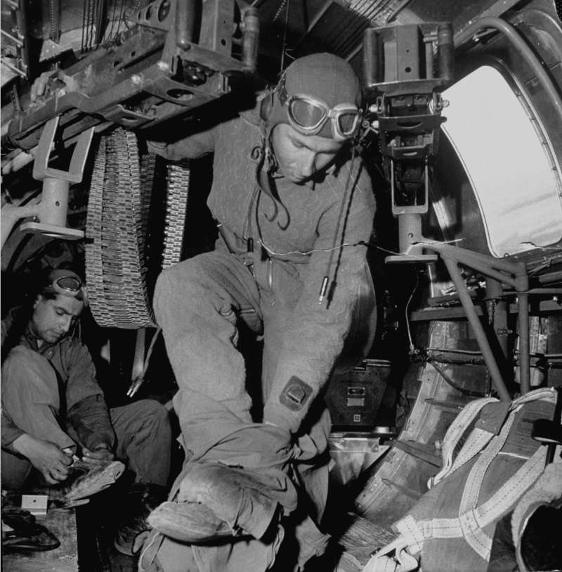 A ball-turret gunner takes off his high-altitude clothing upon return from a sucessful bombing mission at a Sahara desert airdrome in 1943.
