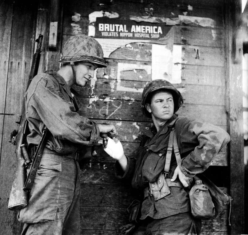 Field Dressing                              An American soldier stands nonchalantly while another bandages his hand during the campaign to retake the Philippines from occupying Japanese forces, Leyte, Philippines, October 1944. The pair lean against a wall which has a torn Japanese propaganda poster which reads,  Brutal America Violates Nippon Hospital Ship.