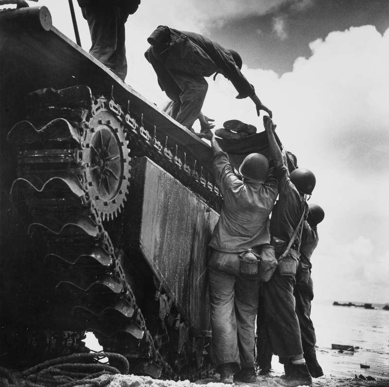 A wounded American Marine is loaded onto an  alligator  amphibious vehicle for evacuation during fighting at Guam's Asan Point in 1944.  W. Eugene Smith's deceptively simple image (reminiscent, in its skyward-reaching composition, of Gericault's masterpiece,  The Raft of the Medusa ) perfectly contrasts the strength, camaraderie, and gentleness of the troops with the mute, utilitarian machinery of war.