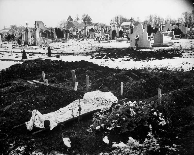 A lace curtain shrouds the body of an American soldier awaiting burial in the Bastogne cemetery.