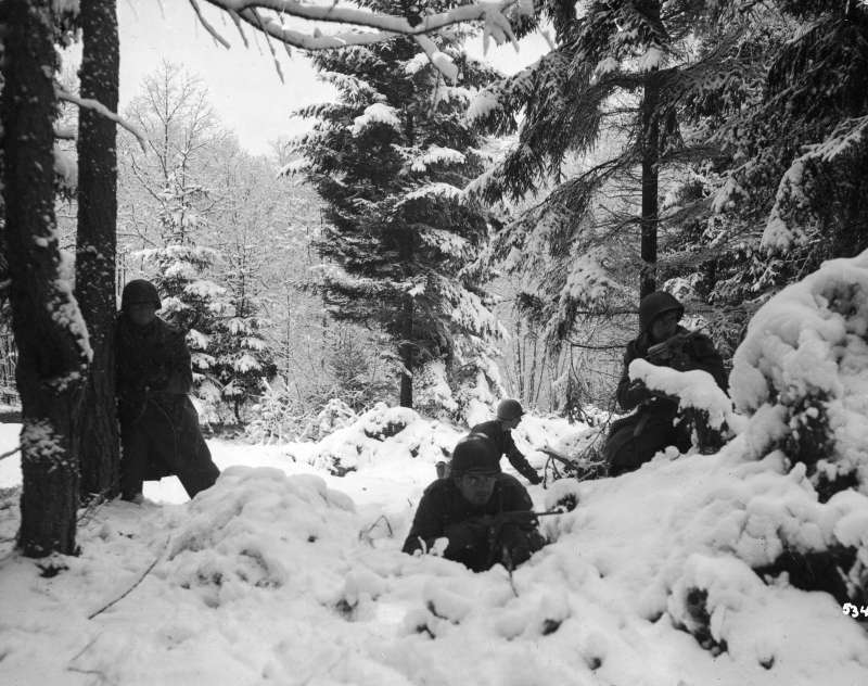 American infrantry from the 290th Regiment crouch in snowy woods near Amonines, Belgium, January 1945.