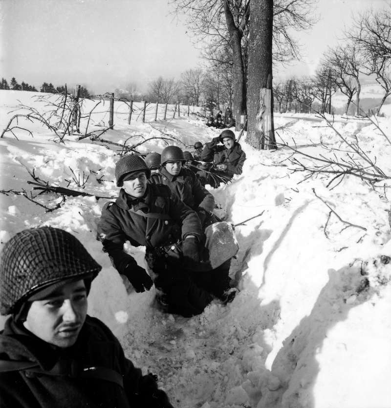 American soldiers in a snowy ditch in Belgium during the Battle of the Bulge