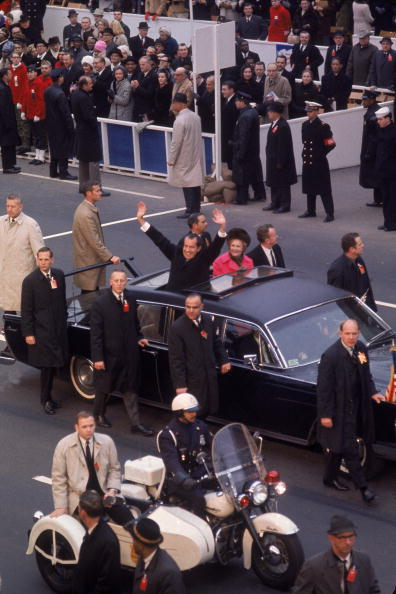 On January 20, 1969, surrounded by Secret Service men, Richard M. Nixon waves from his limo on the way to his Inauguration.  After the assassination of John F. Kennedy, presidential security was beefed up.