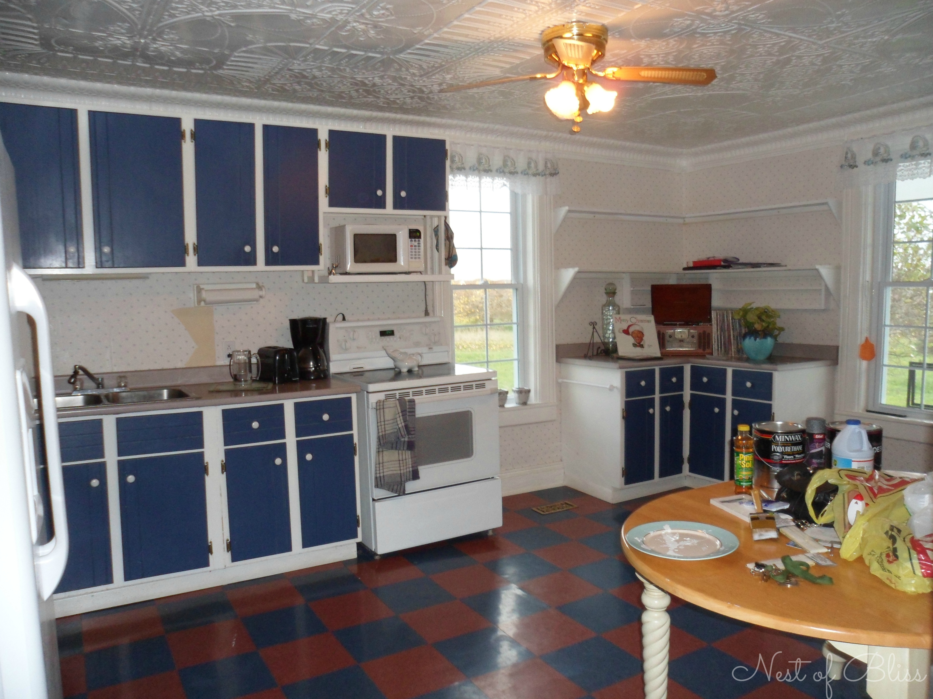 Even after removing the dated wallpaper, garish blue paint on the cabinets and a bold checkered floor detracted from the kitchen's gracious size and lovely tin ceiling.