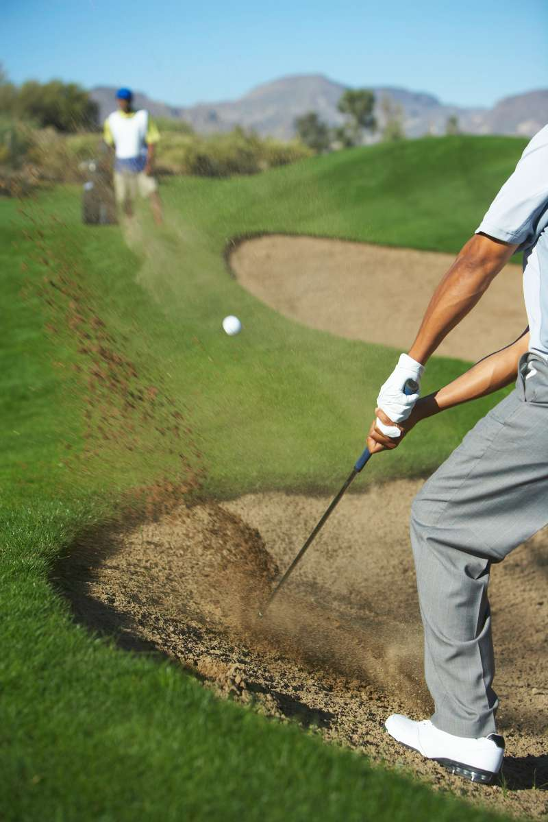 digging golf ball out of bunker