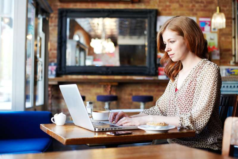 Generation X woman in coffee shop on laptop