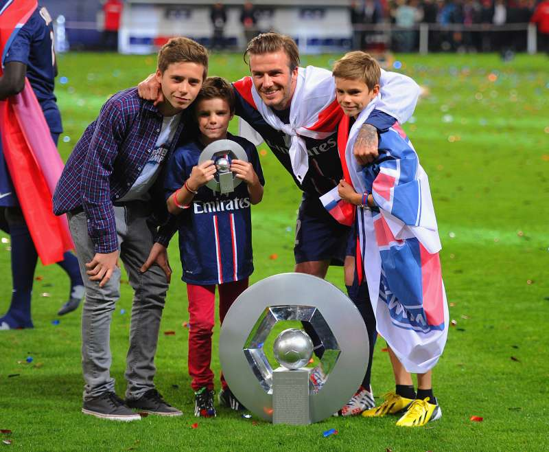 David Beckham posing with the Ligue 1 trophy and his sons