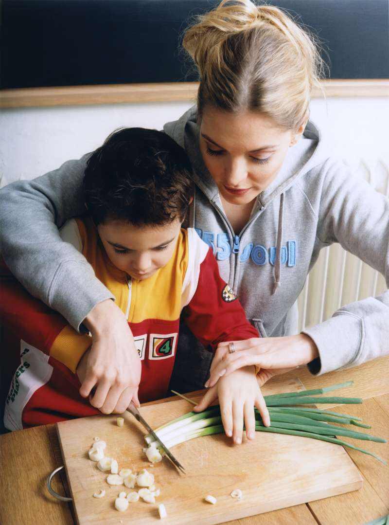 College student teaching child to cook.