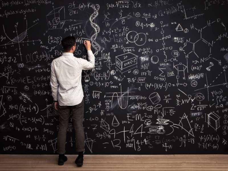 Man writing formulas on a chalkboard