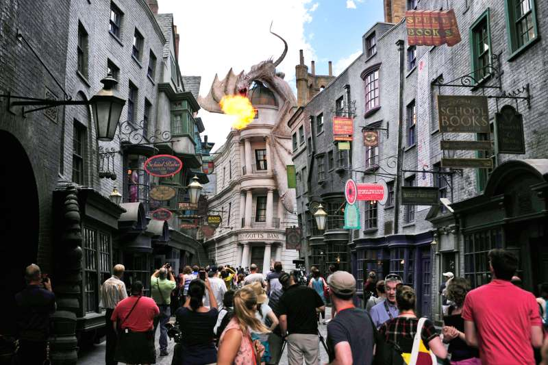 A dragon breathes fire above The Wizarding World of Harry Potter-Diagon Alley during a media preview