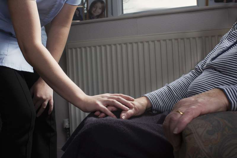 Younger person assisting elderly client.