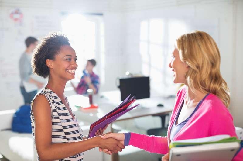 Businesswomen saying hi in an office