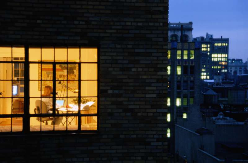 Nighttime exterior view of apartment window with woman working on laptop