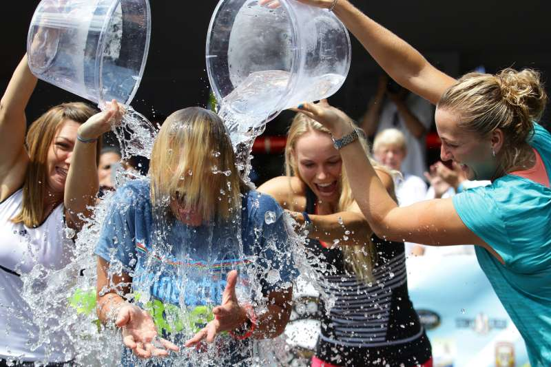 Tournament Director Anne Worcester takes the ALS Ice Bucket Challenge with the help of Tennis players Simona Halep, (left), Caroline Wozniack, (centre), and Petra Kvitova, (right), during the Connecticut Open at the Connecticut Tennis Center at Yale, New Haven, Connecticut, August 17, 2014.