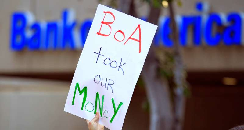 A protester holds up a sign in front of the Bank of America as a coalition of organizations march to urge customers of big banks to switch to local credit unions in San Diego California November 2, 2011.