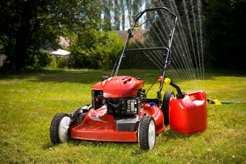 Red lawn mower and sprinkler on lawn