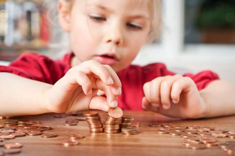 toddler counting pennies on table