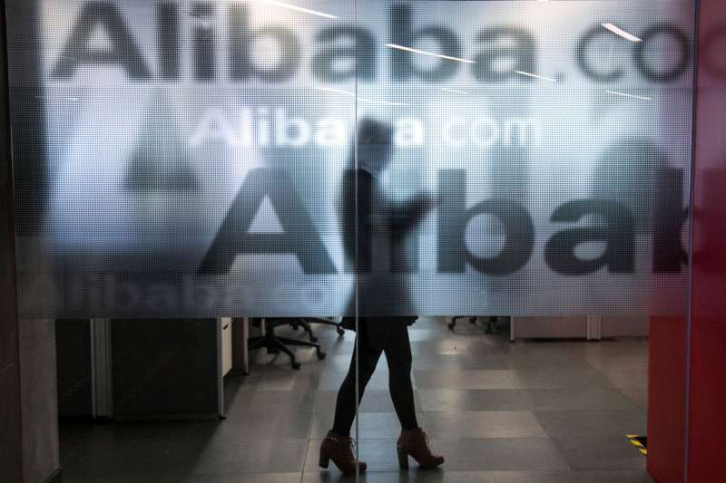 An employee is seen behind a glass wall with the logo of Alibaba at the company's headquarters on the outskirts of Hangzhou, Zhejiang