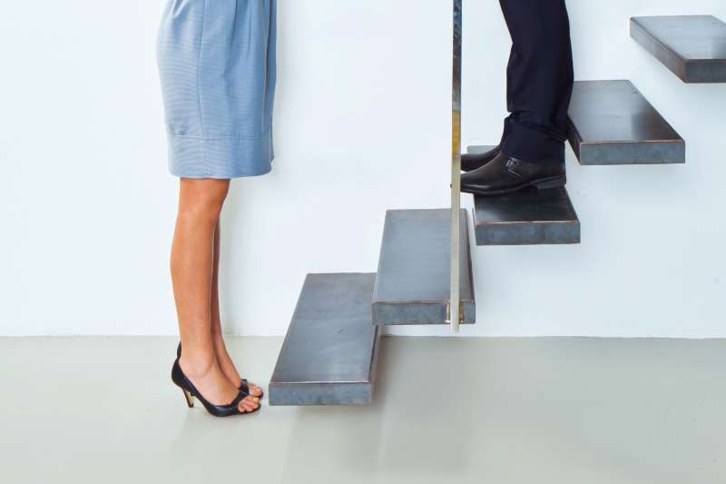woman standing at bottom of steps with man standing above her