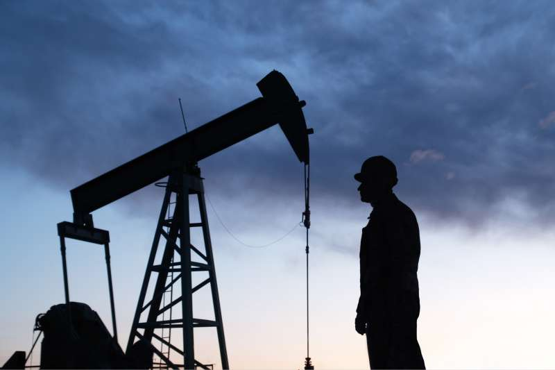 Man looking at oil rig in silhouette
