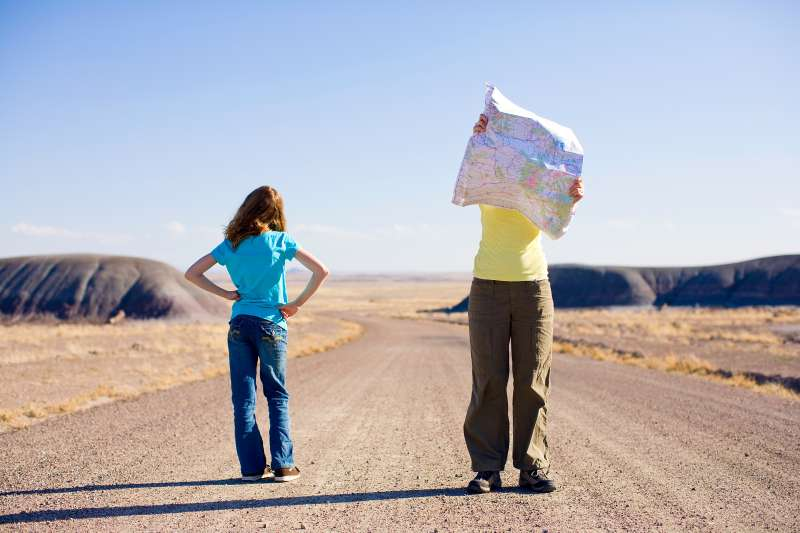 millennials looking at map on road