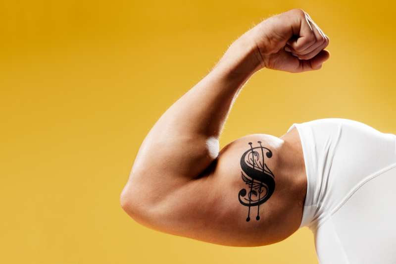 Man flexing arm with $ tattoo on it
