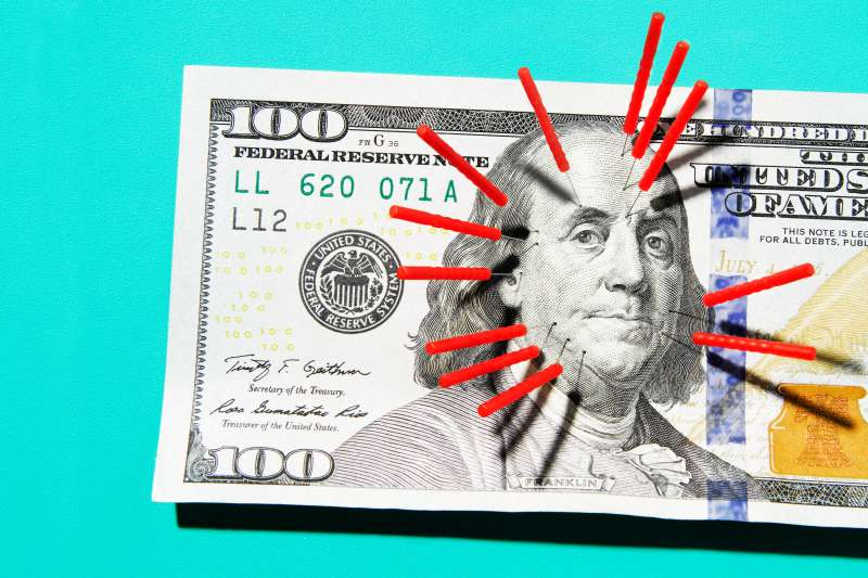 Acupuncture needles stuck in $100 bill