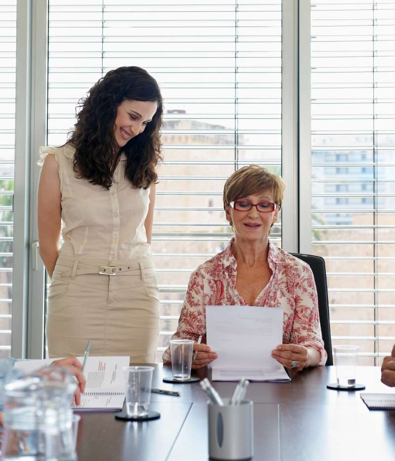 Woman CEO reviewing paper by female employee