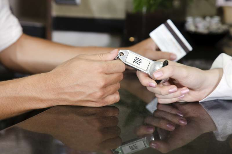 Handing Hotel Key and Credit Card at hotel reception desk