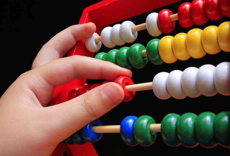 child's hand moving an abacus