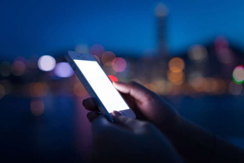 Person using iPhone at night