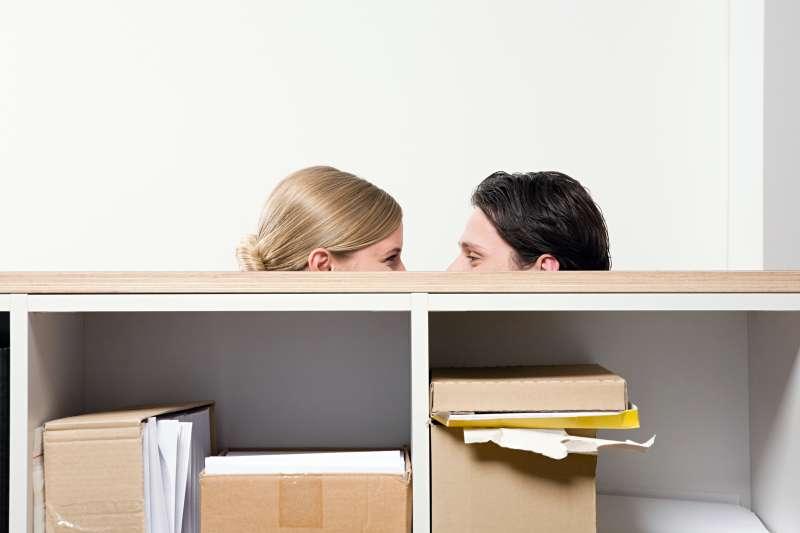 man and woman behind shelving unit