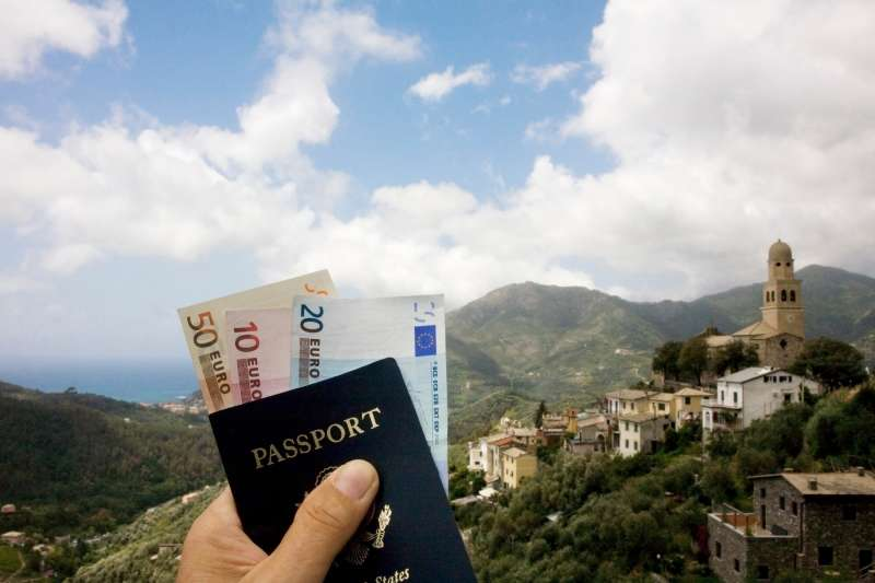 Passport and Euros in front of Italian landscape
