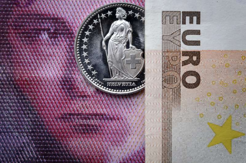 A Swiss coin is seen beneath a euro banknote on Januay 15, 2015 in Lausanne. In a shock announcement on January 15, Switzerland's central bank said it was ending a three-year bid to artificially hold down the value of the Swiss franc against the euro, in a move that immediately sent the safe haven currency soaring.