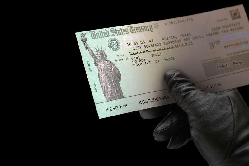 black glove holding US Treasury check