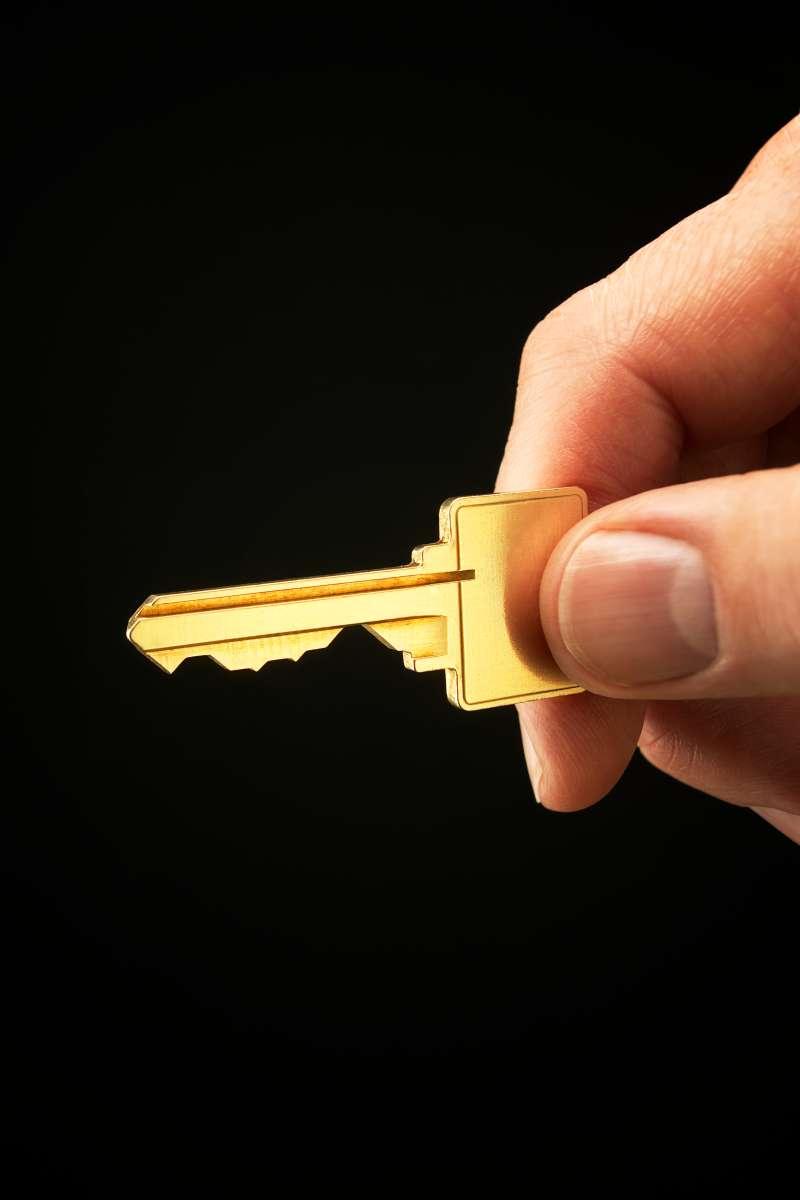 Hand holding gold key, close-up