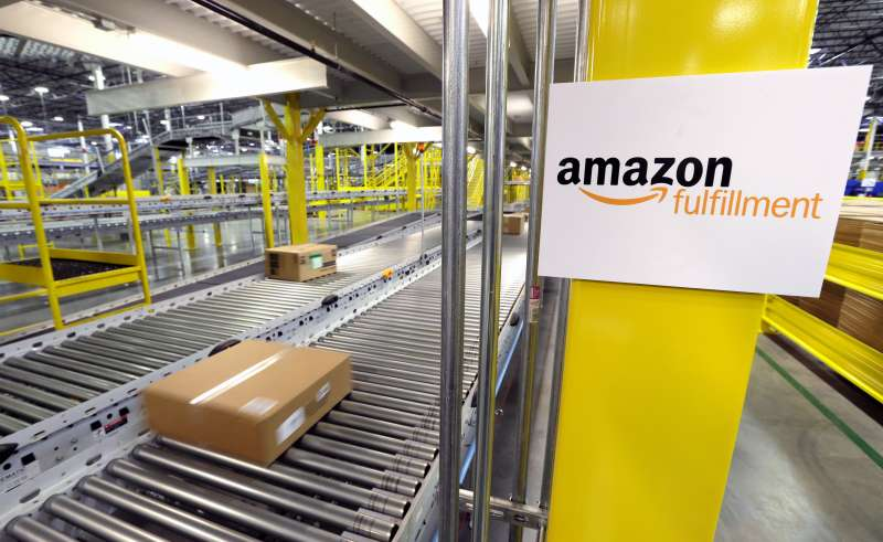 A package moves along a conveyer belt, at a new Amazon.com fulfillment center in DuPont, Wash. The center is one of 50 around the country and three in the Puget Sound area that process and ship Amazon customer orders using a mix of robotic technology and human employees.