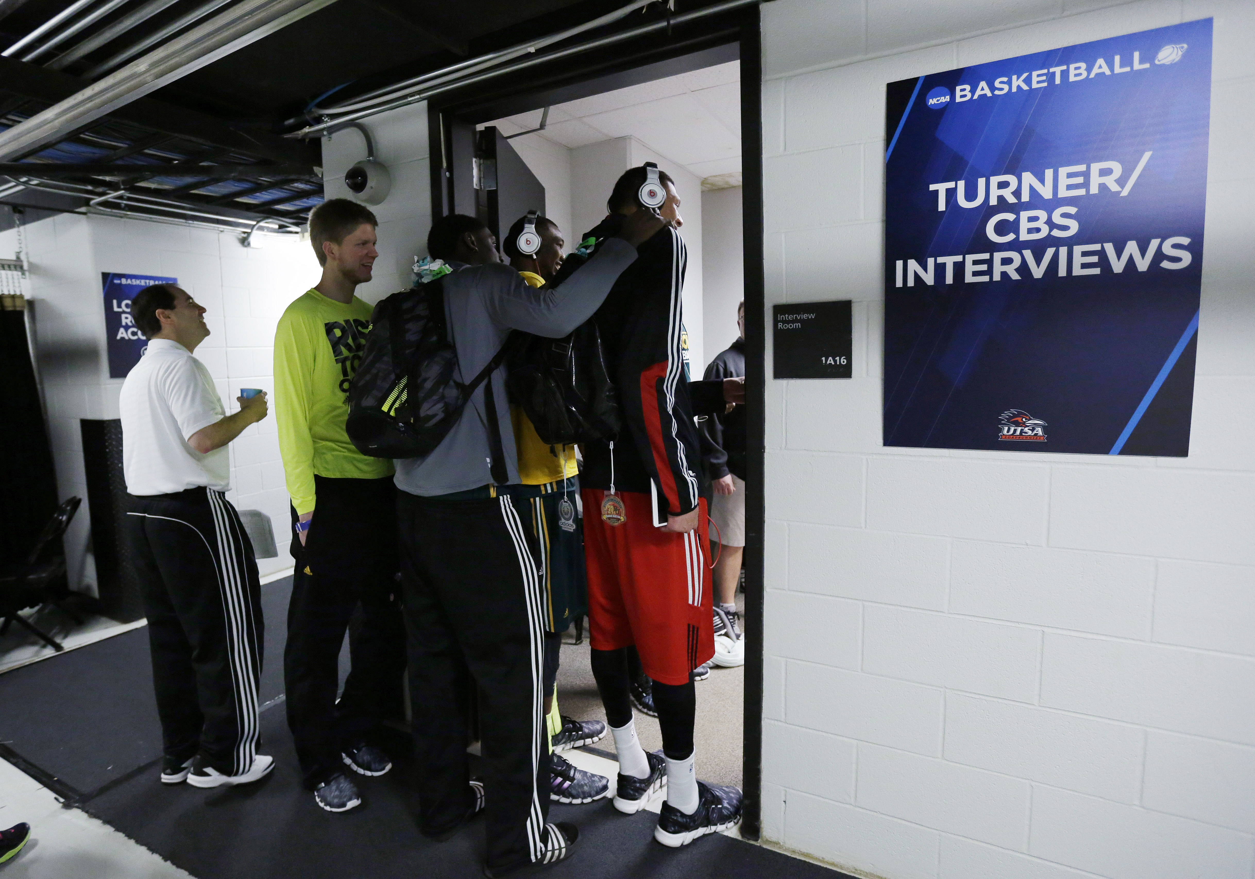 Baylor coach Scott Drew, left, and members of the team including Isaiah Austin, right, peak in on the CBS crew following a news conference at the NCAA college basketball tournament, Saturday, March 22, 2014, in San Antonio.