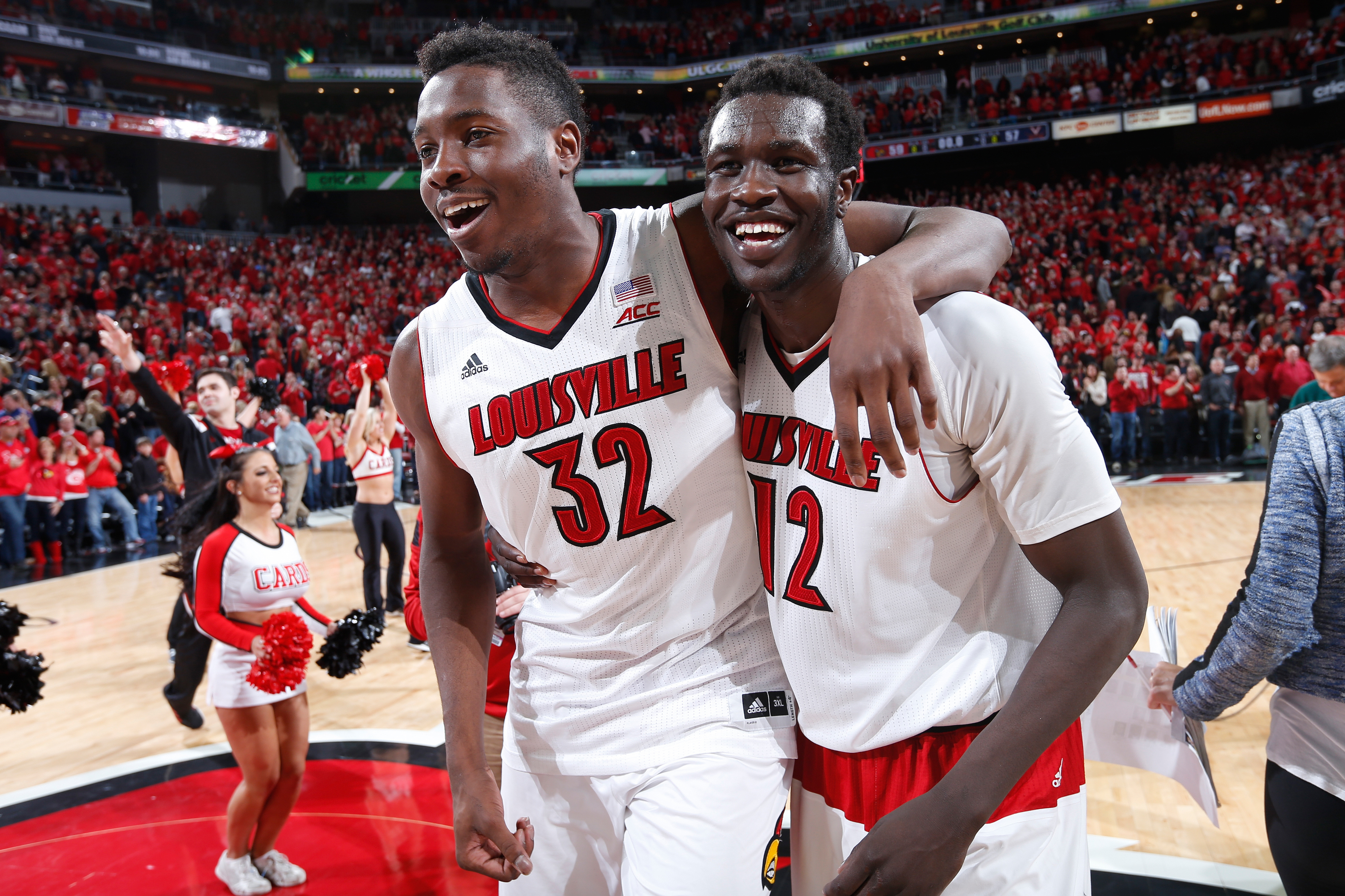 Mangok Mathiang #12 of the Louisville Cardinals celebrates his winning basket with teammate Chinanu Onuaku #32 after the game against the Virginia Cavaliers at KFC Yum! Center on March 7, 2015 in Louisville, Kentucky. Louisville defeated Virginia 59-57.