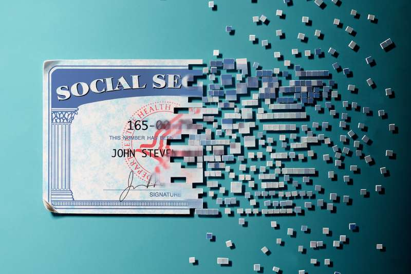 social security card breaking up into bits and floating away