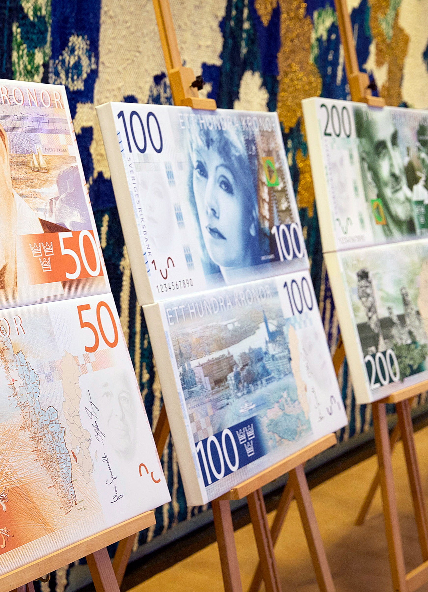 Artwork showing the designs of new folding Swedish krona, or kronor, currency notes due to be issued in 2014 stands on display at the Riksbank in Stockholm, Sweden, on Tuesday, Jan. 22, 2013.