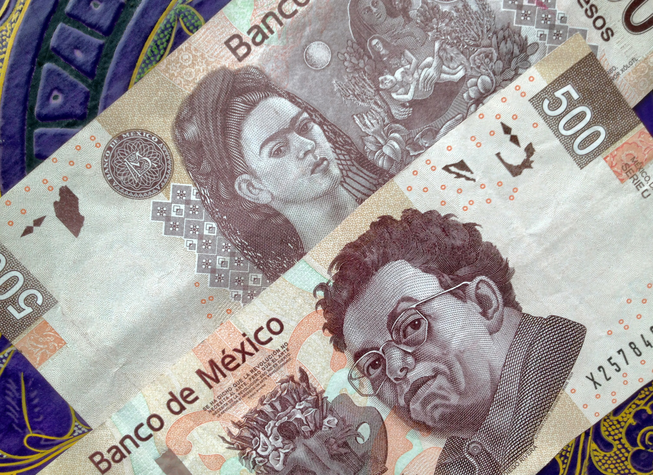 500 Mexican pesos notes on a table with traditional Mexican ornament. The note has the portrait of the painter Diego Riviera on one side and Frida Kahlo on the other.